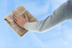 Sluit omhoog van het schoonmakende venster van de vrouwenhand met doek Royalty-vrije Stock Afbeeldingen