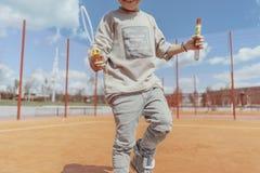 Sluit omhoog van het skateboading van en het maken van bellenjongen bij kleurrijke speelplaats stock afbeelding