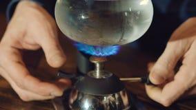 Sluit omhoog van het voorbereiden van koffie in alternatief vacuümkoffiezetapparaat langzaam stock footage
