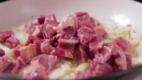 Sluit omhoog van het zetten van rundvlees in hete pan met het braden van uien stock videobeelden