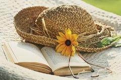 Sluit omhoog van hoed, zonnebril en boek op een hangmat Stock Fotografie