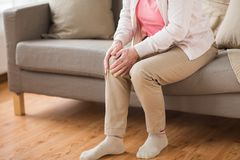 Sluit omhoog van hogere vrouw met pijn in been thuis stock foto's