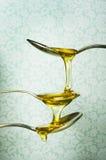 Sluit omhoog van honing die van lepels druipen Stock Fotografie
