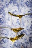 Sluit omhoog van honing die van lepels druipen Royalty-vrije Stock Foto's