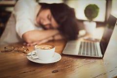 Sluit omhoog van hoogtepunt van koffie in koffiekop met bedrijfsvrouw die van het werken en laptop computerachtergrond wordt verm stock fotografie