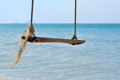 Sluit omhoog van houten schommeling op strand met zonnige dag overzeese achtergrond Royalty-vrije Stock Foto's