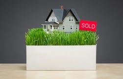 Sluit omhoog van huismodel met gras en verkochte tablet Stock Afbeelding