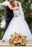 Sluit omhoog van huwelijksboeket met bruid en bruidegom stock afbeeldingen