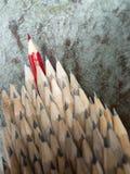 Sluit omhoog van identieke grafietpotloden en één rode het leiden crayo Royalty-vrije Stock Afbeeldingen