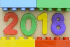Sluit omhoog van jaar 2018 in kleurrijke plastic aantallen die door plastic stuk speelgoed blokken worden omringd Royalty-vrije Stock Foto