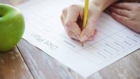 Sluit omhoog van jong vrouw het schrijven dieetplan thuis stock video