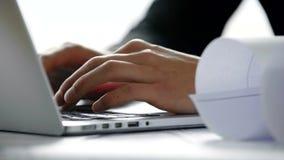 Sluit omhoog van jonge architectenhanden typend op laptop computertoetsenbord in wit modern bureau in de zonnige dag op stock videobeelden