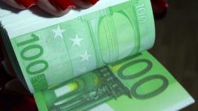 Sluit omhoog van jonge bedrijfsvrouw met pak van geld in handen met rode spijkers stock footage