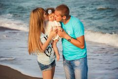 Sluit omhoog van jonge gelukkige houdende van familie die en kleine dochter koesteren kussen bij strand samen dichtbij oceaan, ge stock fotografie