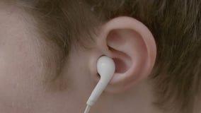 Sluit omhoog van jonge jongen die oortelefoons in zijn oor zetten om aan muziek te luisteren en dan hen verwijderen toe te schrij stock video