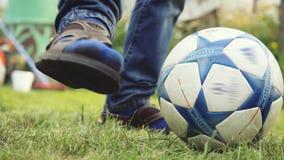 Sluit omhoog van jonge jongens` s benen spelend met de schoppen van de voetbalbal op het gras in de zomer zonnige dag in langzame stock video