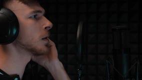 Sluit omhoog van jonge knappe jongen die emotioneel lied zingen Het dramatische zingen bij professionele vocale studio Studiorepe stock footage