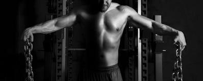 Sluit omhoog van jonge spiermens het opheffen gewichten Royalty-vrije Stock Foto's