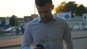Sluit omhoog van jonge succesvolle zakenman in overhemd die zich bij stedelijk milieu bevinden en smartphone gebruiken bij zonson stock videobeelden
