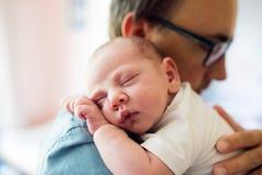 Sluit omhoog van jonge vader die zijn pasgeboren babyzoon houden stock foto