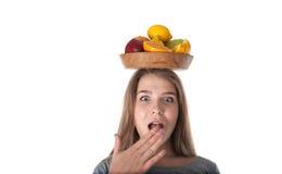 Sluit omhoog van jonge verraste vrouw wat een houten kom met vruchten houdt: appelen, sinaasappelen, citroen Vitaminen en het gez Stock Foto's