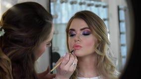 Sluit omhoog van jonge vrouw die permanente lippenmake-up krijgen bij schoonheidssalon stock videobeelden