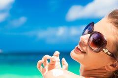 Sluit omhoog van jonge vrouw die in zonnebril zonroom op schouder zetten Royalty-vrije Stock Foto's