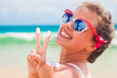 Sluit omhoog van jonge vrouw die in zonnebril zonroom op schouder zetten stock afbeelding