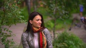 Sluit omhoog van jonge vrouw, het mooie donkerbruine vrouw glimlachen in de zomerpark 4 K stock video