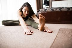 Sluit omhoog van jonge vrouw het praktizeren yoga, zittend in Hoofd aan Knie buig vooruit oefening, stelt Janu Sirsasana, huis bi royalty-vrije stock afbeelding