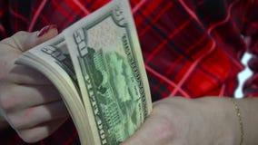 Sluit omhoog van jonge vrouw in rode kledingstellingen een pak van geld binnen langzame motie indient stock videobeelden