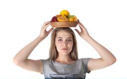 Sluit omhoog van jonge vrouw wat een houten kom met vruchten houdt: appelen, sinaasappelen, citroen Vitaminen en het gezonde eten Stock Foto