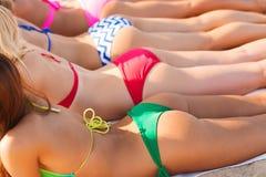 Sluit omhoog van jonge vrouwen liggend op strand Royalty-vrije Stock Afbeeldingen