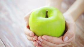 Sluit omhoog van jonge vrouwenhanden die groene appel tonen stock footage