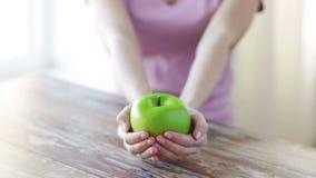 Sluit omhoog van jonge vrouwenhanden die groene appel tonen stock videobeelden