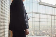 Sluit omhoog van jonge zakenman in zwart kostuum gebruikend smartphone terwijl het blijven op zijn kantoor royalty-vrije stock foto's
