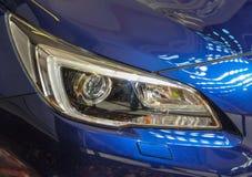 Sluit omhoog van juiste koplamp van de blauwe sportwagen stock afbeelding
