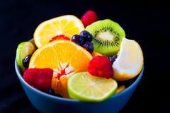 Sluit omhoog van kant van kom met de kleurrijke natte verse zomer en spring vruchten zoals sinaasappelen en kiwi op zwarte achter royalty-vrije stock afbeeldingen