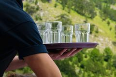 Sluit omhoog van kelners` s handen houdend dienblad met waterglazen stock afbeelding