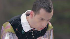 Sluit omhoog van kerel in nationaal kostuum die de auto'svoorruit schoonmaken stock video