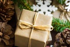 Sluit omhoog van Kerstmis en Nieuwjaargiftvakje in ambachtdocument wordt verpakt, houten ornamenten, sneeuwvlok, sparrentakken, d Stock Afbeeldingen