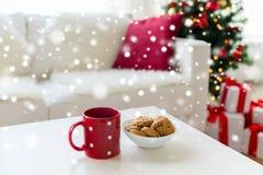 Sluit omhoog van Kerstmiskoekjes en rode kop op lijst Stock Afbeeldingen