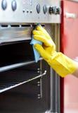 Sluit omhoog van keuken van de vrouwen de schoonmakende oven thuis royalty-vrije stock foto's