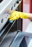 Sluit omhoog van keuken van de vrouwen de schoonmakende oven thuis stock foto