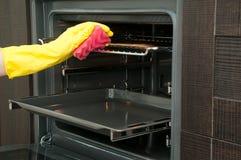 Sluit omhoog van keuken van de vrouwen de schoonmakende oven thuis royalty-vrije stock foto
