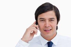 Sluit omhoog van kleinhandelaar het spreken op zijn cellphone Stock Afbeeldingen