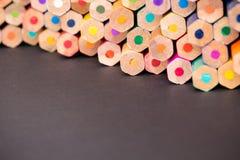 Sluit omhoog van kleurenpotloden op zwarte oppervlakte Stock Afbeeldingen