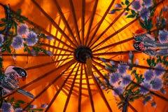 Sluit omhoog van kleurrijke oranje die document paraplu met bloemen wordt en door zonlicht wordt verlicht geschilderd die - Chian royalty-vrije stock afbeeldingen