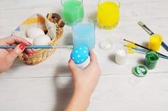 Sluit omhoog van kleurrijke paaseieren in een mand Borstel en verf Stock Afbeeldingen