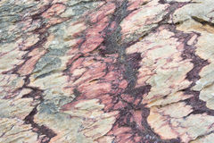 Sluit omhoog van kleurrijke rotsoppervlakte, natuurlijke achtergrond, patroon en textuur Metamorfose wit gevouwen en gebroken kwa stock afbeelding